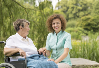 old woman and caregiver showing their genuine smile